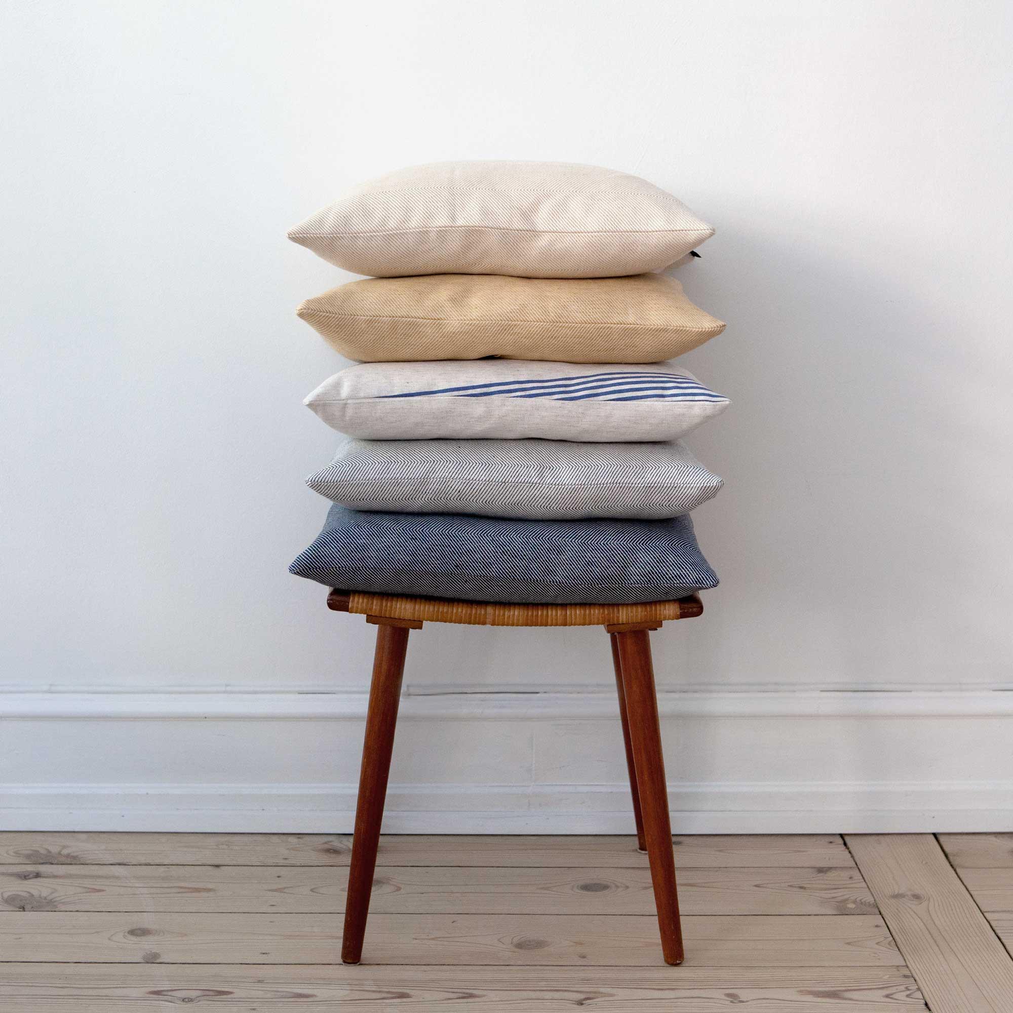 Square cushions in river pattern, hay yellow and indigo herringbone weave, design by Anne Rosenberg, RosenbergCph