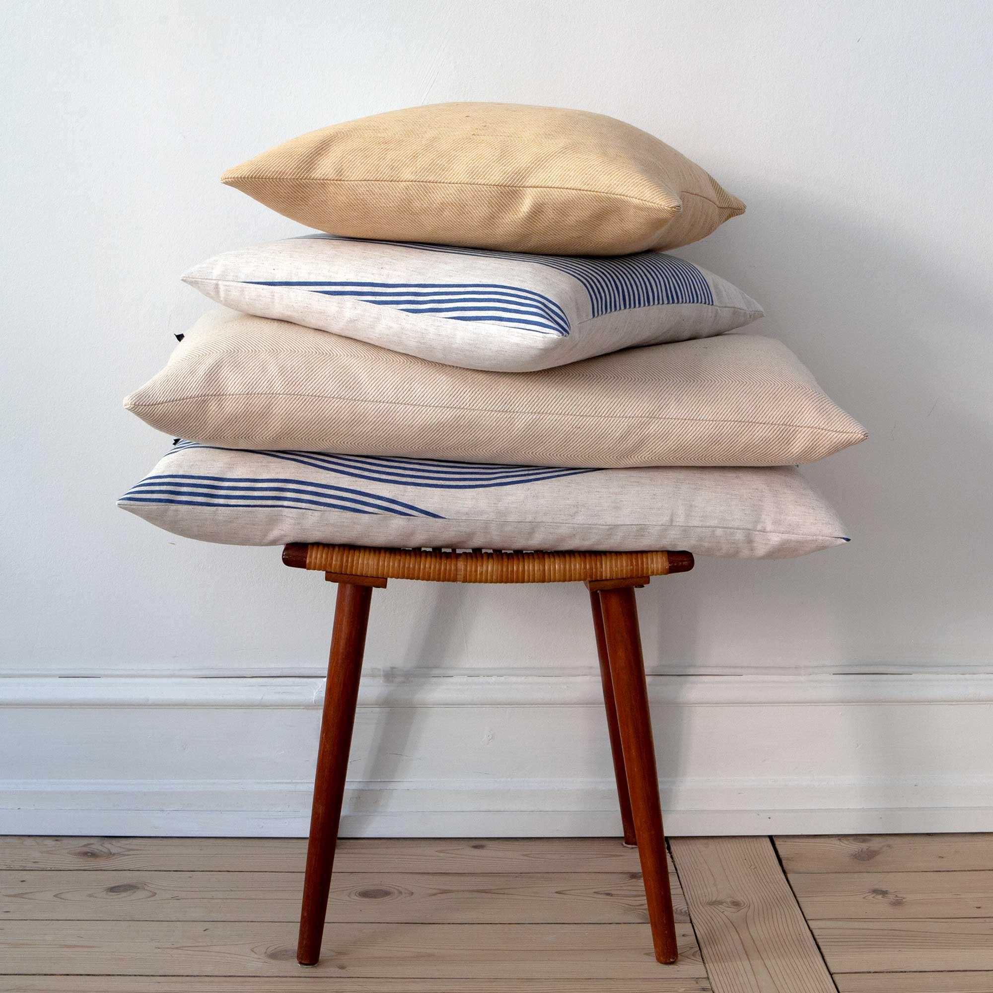 Rectangular cushions in river pattern, hay yellow and indigo herringbone weave, design by Anne Rosenberg, RosenbergCph
