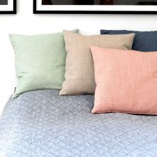 wool and linen cushions on linen bedspread